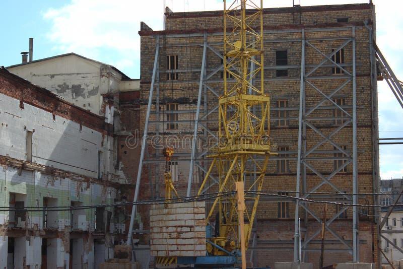 Zniszczenie stary budynek, odbudowa, zmiany strukturalne budowa, wysoki żuraw pracuje na miejscu _ obrazy stock