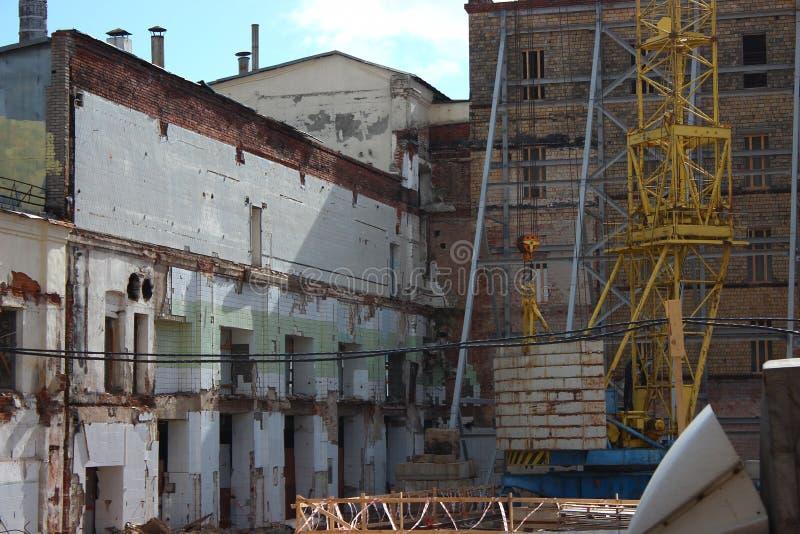 Zniszczenie stary budynek, odbudowa, zmiany strukturalne budowa, wysoki żuraw pracuje na miejscu _ obraz royalty free