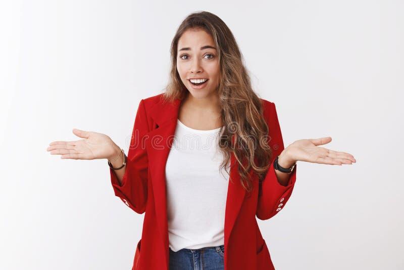 Zo wat Het portret van arrogant unbothered knap modern jong modieuze vrouwen rood jasje, ophalend achteloze handen royalty-vrije stock afbeelding