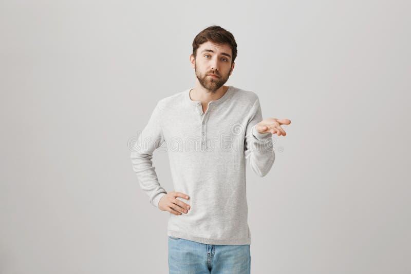 Zo wat uw punt is Niet onder de indruk zijnde en geinteresseerde gehinderde klant die, die hand op taille houden en met palm gest stock afbeeldingen