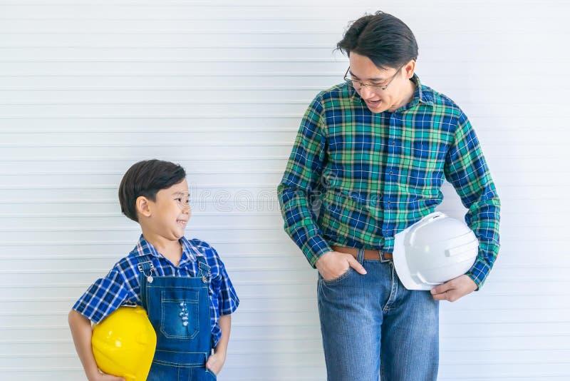 Zoals vader als zoon met een aziatische vader en zoon die werkt in de bouwsector voor Famiyl-bonding en toekomstige carrière stock fotografie