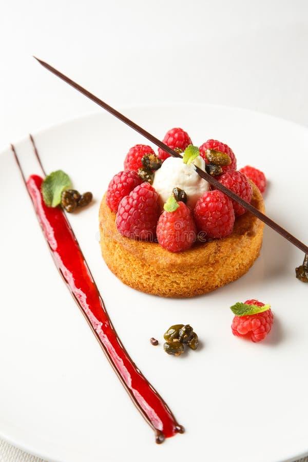 Zobelbretone oder -Keks mit Vanillecreme und -himbeerecoulis auf weißem Teller stockfoto