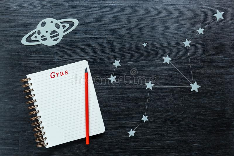 Constellations Grus. Zodiacal star, constellations Grus on a black background with a notepad and pencil stock images