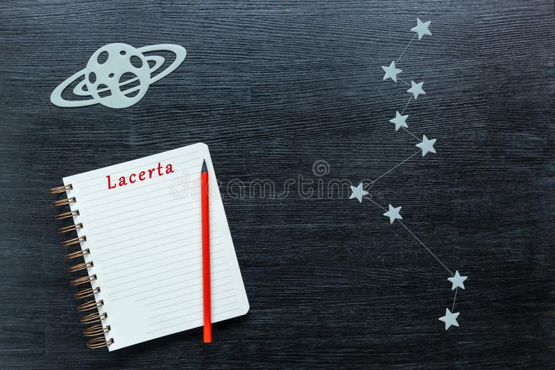 Constellations Lacerta. Zodiacal star, constellations Lacerta on a black background with a notepad and pencil royalty free stock image