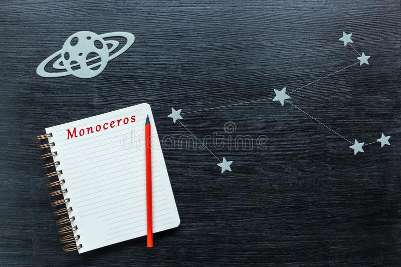 Constellations Monoceros. Zodiacal star, constellations Monoceros on a black background with a notepad and pencil royalty free stock photos