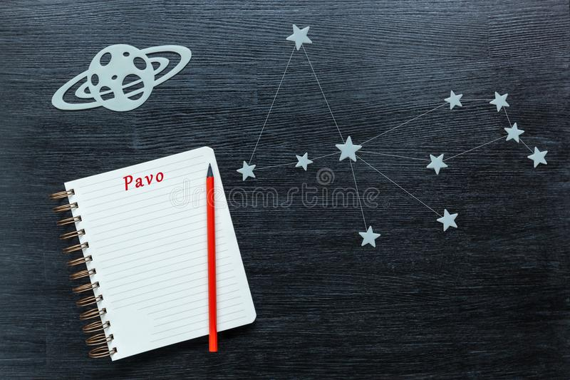 Constellations Pavo. Zodiacal star, constellations Pavo on a black background with a notepad and pencil royalty free stock photography