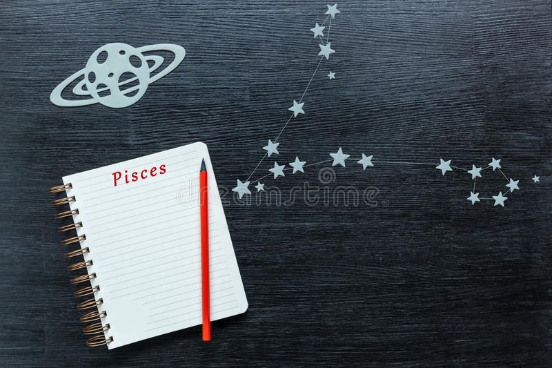 Constellations Pisces. Zodiacal star, constellations Pisces on a black background with a notepad and pencil royalty free stock images