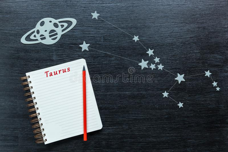 Constellations Taurus. Zodiacal star, constellations Taurus on a black background with a notepad and pencil stock photos