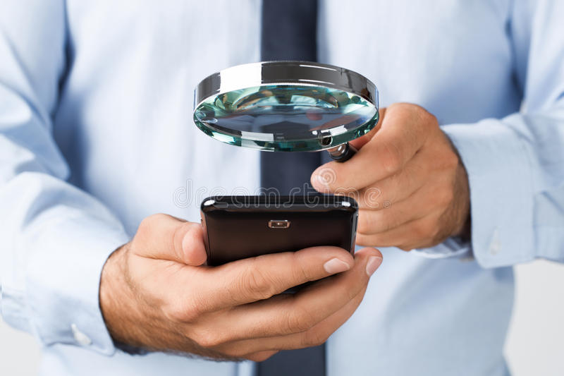 Zoeken, die op de mobiele telefoon spioneren stock fotografie