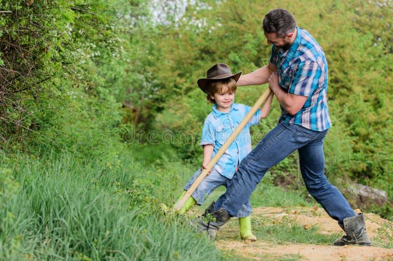 Zoeken naar schatten Kleine jongen en vader met schop op zoek naar schatten Geest van avonturen Adventure jacht voor stock afbeeldingen
