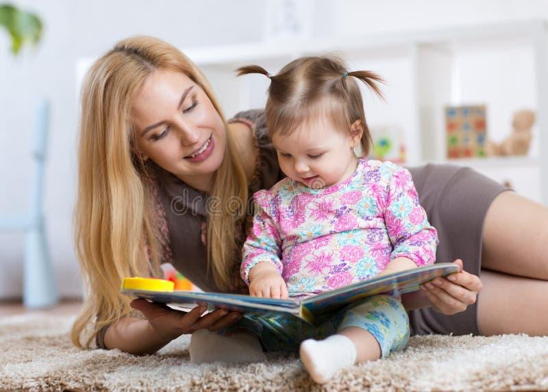 Zoet babymeisje met het boek van de moederlezing in kinderdagverblijf stock foto