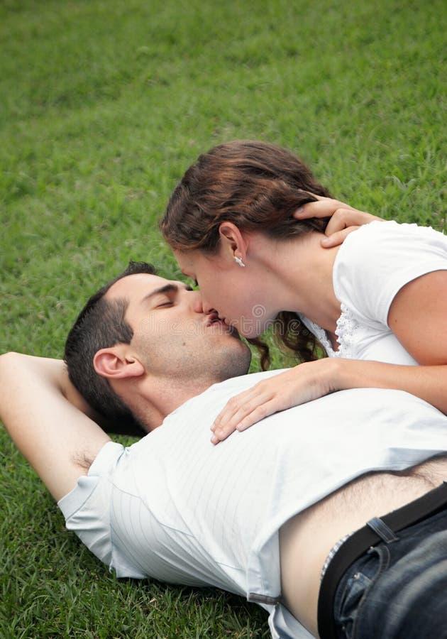 Zoet beeld van het jonge paar kussen op het gras royalty-vrije stock foto
