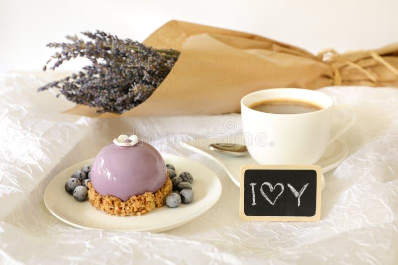 Zoet de tijdconcept van het ochtendontbijt, mooie violette cake, bosbessen, kop van koffie dichtbij plaat met nota I liefde stock foto