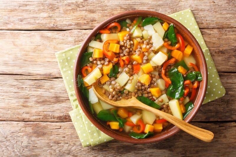 Zoet gekookte linzen soep met groenten en spinazie in een kom op tafel horizontale bovenaanzicht stock foto's