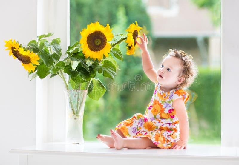Zoet krullend babymeisje naast zonnebloemboeket stock afbeeldingen