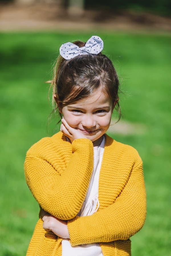 Zoet meisje in openlucht met geel jasje die zich bij het park bevinden royalty-vrije stock foto