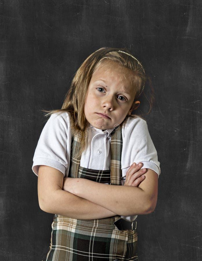 Zoet ondergeschikt schoolmeisje met blondehaar schreeuwen droevig voor het bord van het schoolklaslokaal royalty-vrije stock foto