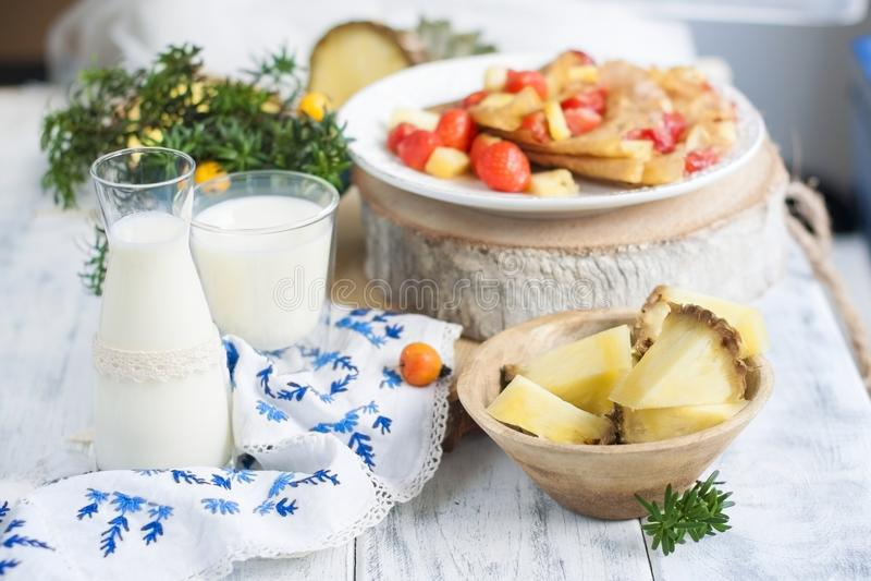 Zoet ontbijt met melk Pannekoeken en verse die bessen van aardbeien en ananas, met gepoederde suiker worden bestrooid stock afbeeldingen