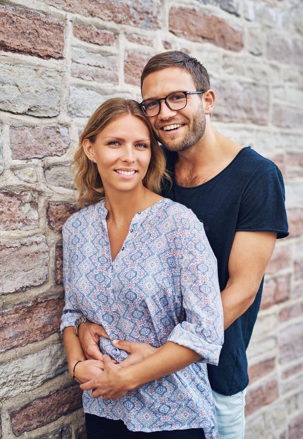 Zoet Paar tegen Muur en Glimlachen bij Camera royalty-vrije stock afbeelding