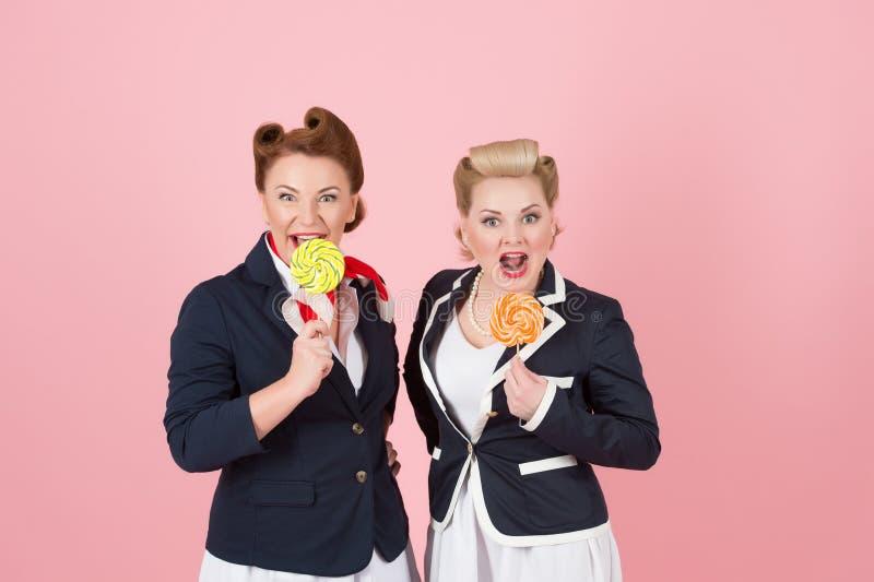 Zoet Paar van meisjes met lollys Speld-op gestileerde vrouwen met in hand suikergoed Twee zoete dames met twee snoepjes royalty-vrije stock foto