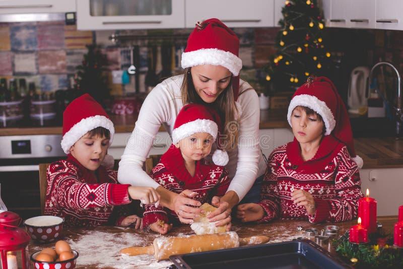 Zoet peuterkind en zijn oudere broer, jongens, die mama helpen die Kerstmiskoekjes thuis voorbereiden stock foto