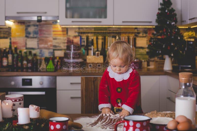 Zoet peuterkind, jongen, die mama helpen die Kerstmiskok voorbereiden royalty-vrije stock fotografie