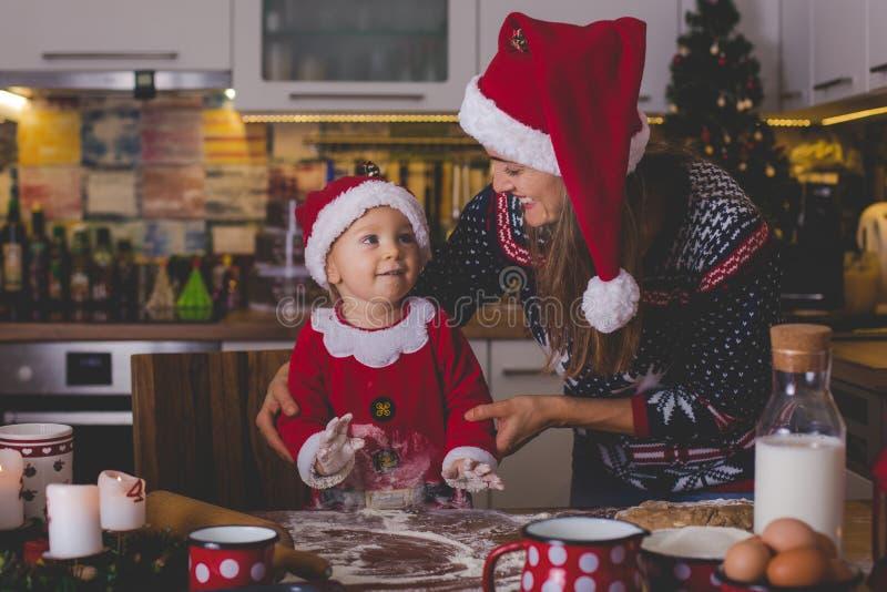 Zoet peuterkind, jongen, die mama helpen die Kerstmiskok voorbereiden stock afbeeldingen