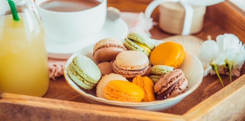Zoet romantisch ontbijt in bed voor minnaar Sluit omhoog makarons, kop van koffie, sap, bloem en giftdoos op houten dienblad Verj stock afbeeldingen