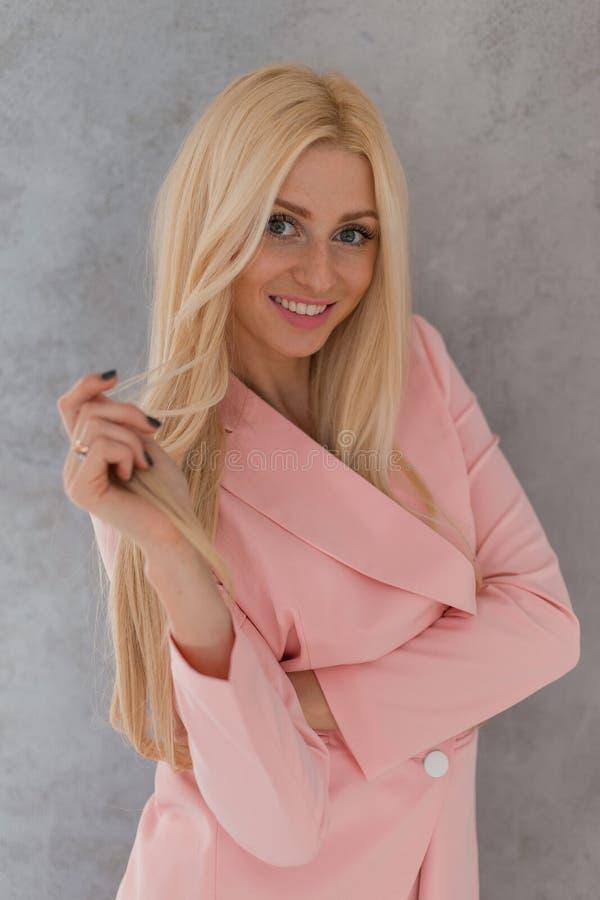 Zoet sensueel blondemeisje in roze modieuze kleren die en het bekijken camera het spelen met haar glimlachen stellen royalty-vrije stock afbeelding