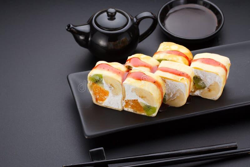 Zoet sushibroodje in mamenori op een steenplaat stock foto's