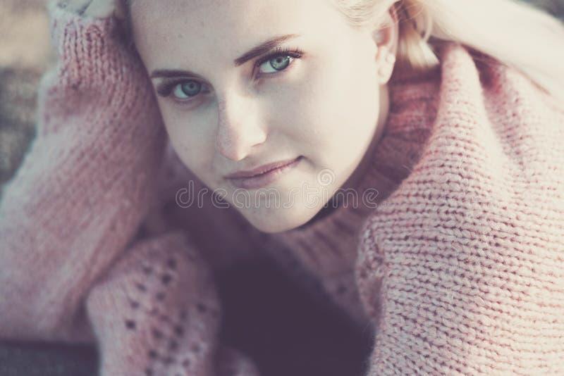 Zoet vertrouwelijk portret van een jonge mooie blonde Kaukasische vrouw die met verbazende blauwe ogen u bekijkt die glimlachen o royalty-vrije stock foto