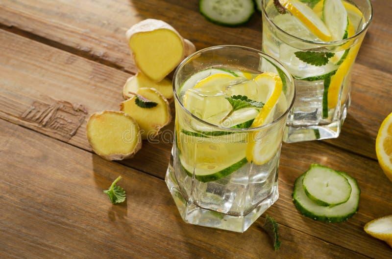 Zoet water met citroen, munt, gember en komkommer op houten stock foto