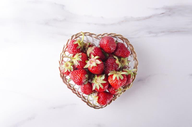 Zoete aardbeien in de kleine mand Symbool van liefde De kom van de hartvorm, de zomer sappige aardbeien stock foto's