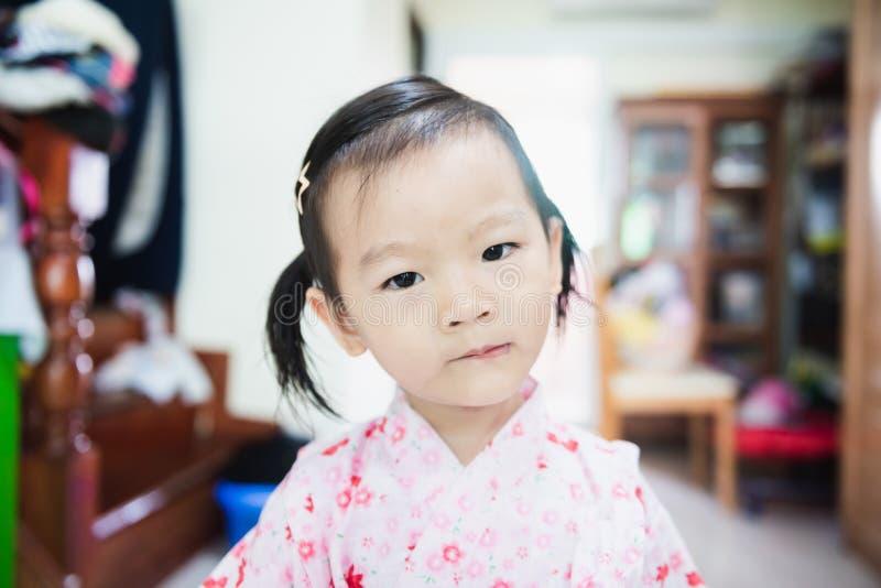 Zoete Aziaat weinig kind met het gezicht van blikaskance, verward concept stock foto's