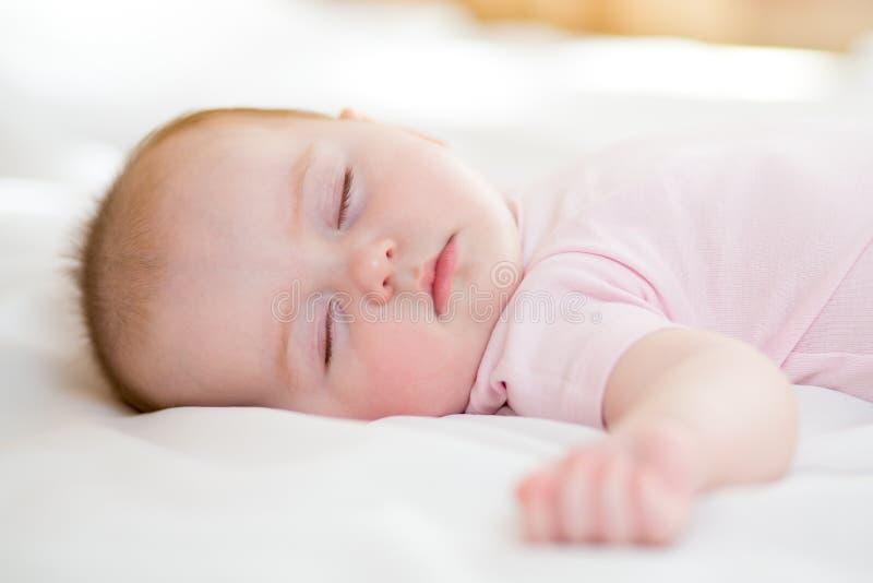 Zoete babyzuigeling die op een bed liggen terwijl het slapen in een heldere ruimte stock fotografie