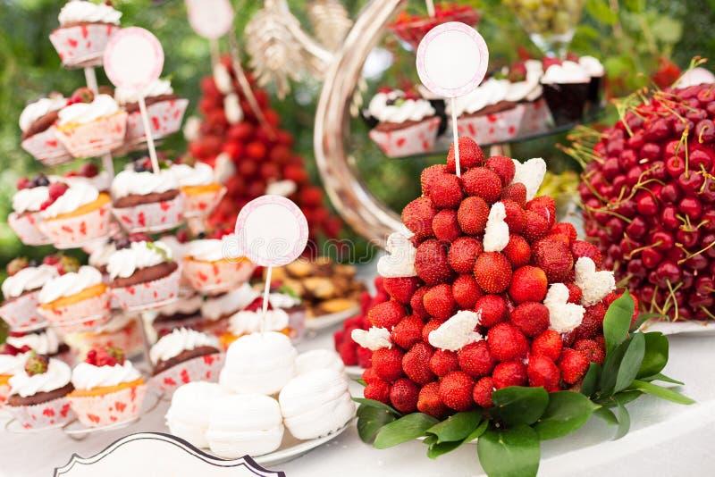 Zoete bar met cupcakes, verse aardbeien stock foto's