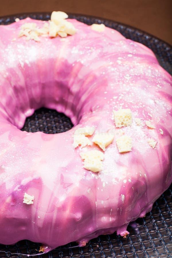 Zoete cake in de vorm van een doughnut, roze suikerglazuur Close-up stock fotografie