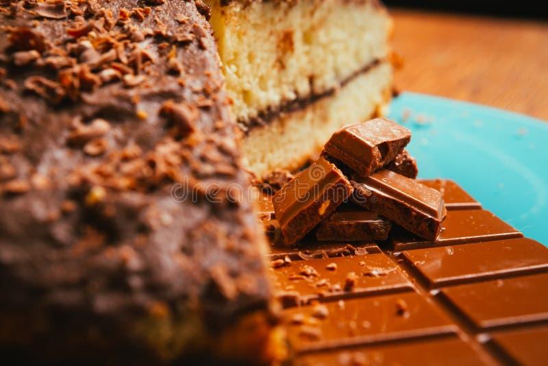 Zoete cake en chocoladeschilfers op een blauwe plaat stock fotografie