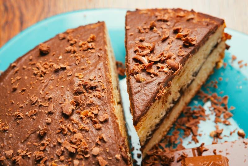 Zoete cake en chocoladeschilfers op een blauwe plaat stock afbeeldingen
