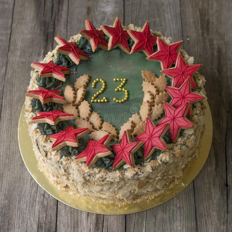 Zoete cake met decor op 23 februari-vakantie op lichte houten achtergrond gestemd stock foto