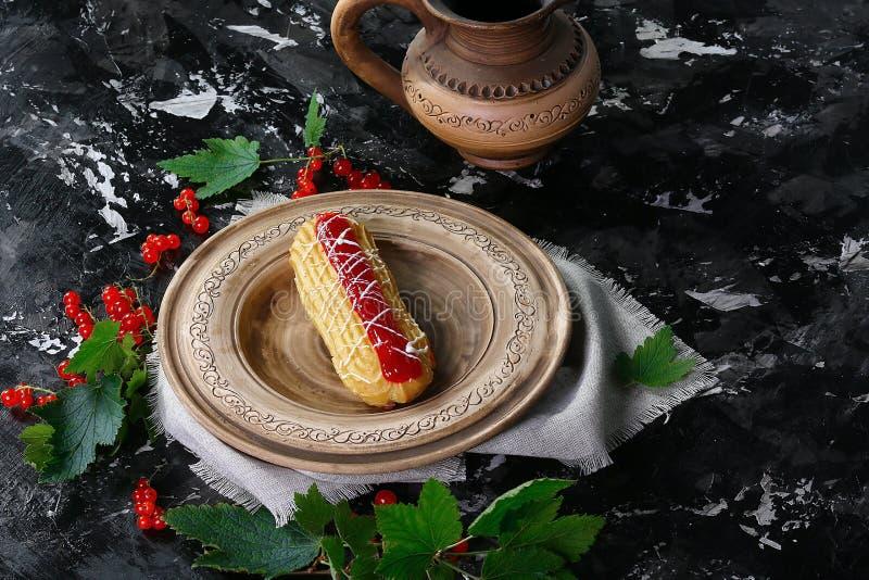 Zoete cake met room, jam met rode bessenbessen op een bruine kleiplaat, op donkere achtergrond Het dessert van het de zomerfruit  royalty-vrije stock foto