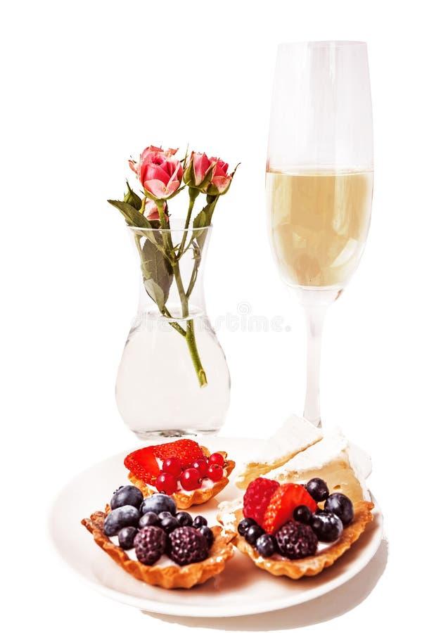 Zoete cakes met bessen en champagne stock fotografie