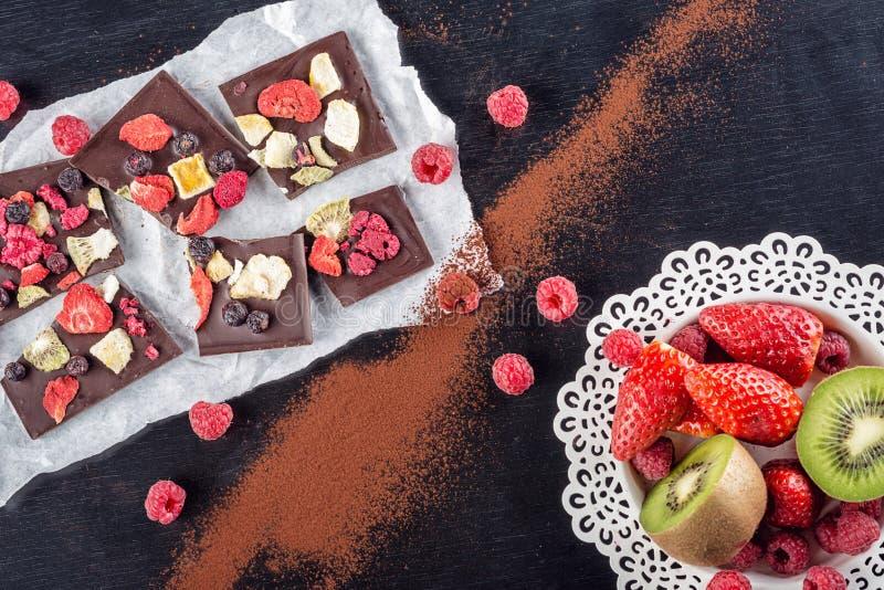 Zoete chocoladeplakken met vruchten op Witboek met fruit op plaat, zoet dessert op zwarte backgroud beeld voor patisserie stock foto