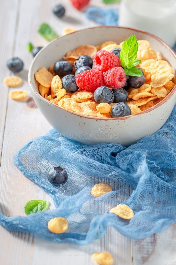 Zoete cornflakes met bessen en melk als gezonde maaltijd stock foto's
