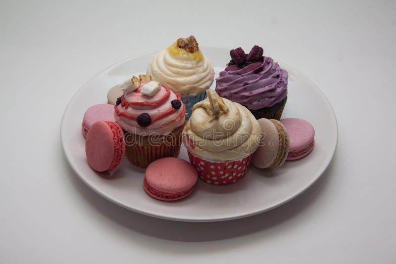 Zoete cupcakes en macarons close-up op wit royalty-vrije stock afbeeldingen