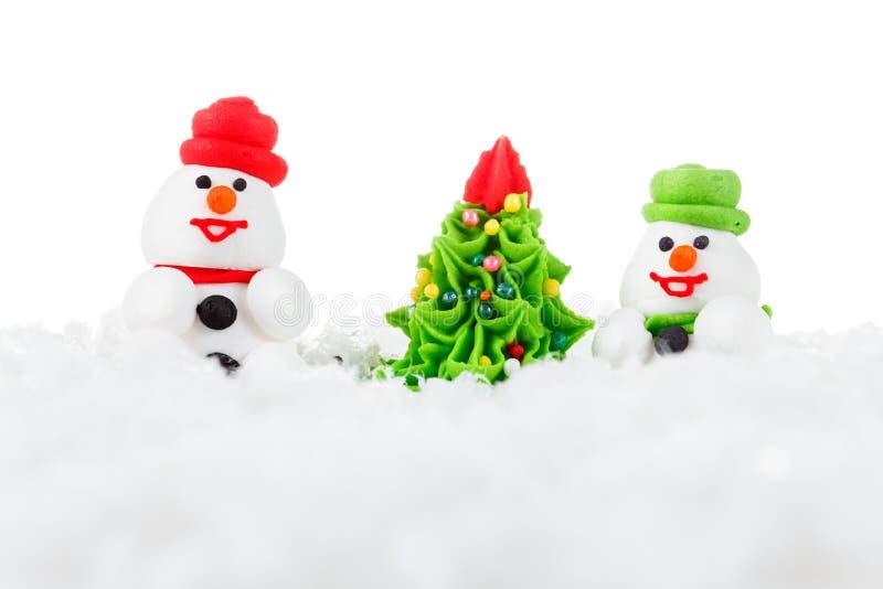 Zoete dessertsneeuwman, sneeuw en Kerstboom met feestelijke decoratie stock foto