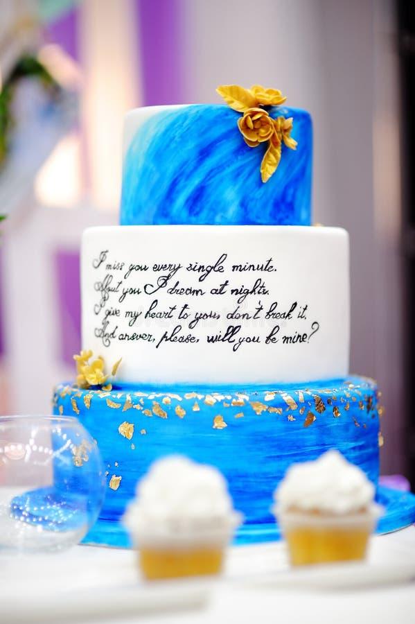 Zoete die lijst met blauwe cake en cupcakes op huwelijkspartij wordt geplaatst stock afbeeldingen