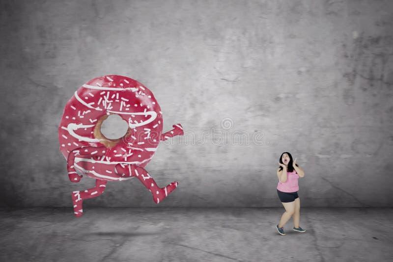Zoete doughnut die vette vrouw achtervolgen stock afbeelding