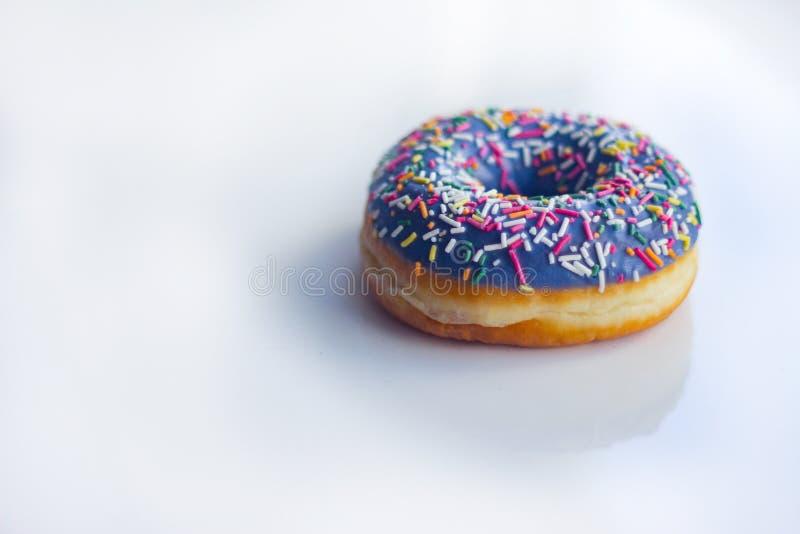 Zoete Doughnut met suikerglazuur en kleur die, op een witte achtergrond bestrooien stock afbeelding