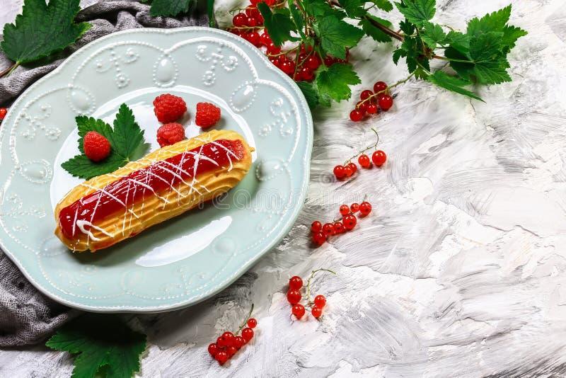 Zoete eclair met bes Frans dessert Eclair het dessert van het vlagebakje met binnen slagroom Hoogste mening Ruimte voor tekst royalty-vrije stock fotografie